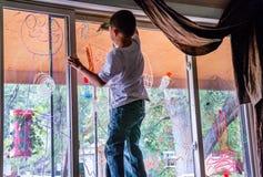 Сочинительство ребенка на окне с стеклянными отметками Стоковые Изображения