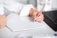 Сочинительство руки бизнес-леди на бумаге Стоковое Фото