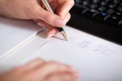 Сочинительство руки бизнес-леди на бумаге Стоковые Изображения