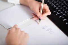 Сочинительство руки бизнес-леди на бумаге Стоковое фото RF
