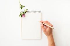 Сочинительство руки женщины на бумажной тетради Стоковое Изображение