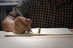 Сочинительство руки на тетради Стоковая Фотография