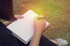 Сочинительство руки ` s маленькой девочки на дневнике Стоковое фото RF