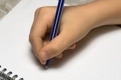 Сочинительство руки ` s ребенка на белом листе тетради Стоковые Изображения