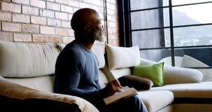 Сочинительство старшего человека на дневнике в живущей комнате 4k сток-видео