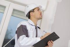 Сочинительство съемщика здания на доске сзажимом для бумаги на строительной площадке Стоковое Изображение