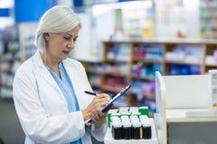 Сочинительство аптекаря на доске сзажимом для бумаги стоковые фото