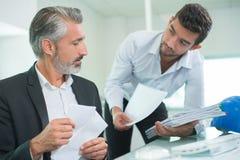 Сочинительство бизнесмена и коллеги на бумаге в офисе Стоковые Изображения