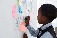 Сочинительство бизнесмена на бумаге на whiteboard в творческом офисе Стоковое Фото