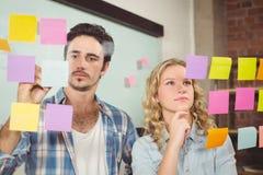 Сочинительство бизнесмена на бумаге пока женщины читая в офисе стоковые фотографии rf