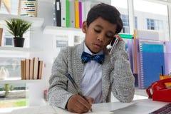 Сочинительство бизнесмена на книге пока говорящ на мобильном телефоне Стоковые Фото