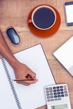 Сочинительство бизнесмена на тетради кофе на столе Стоковые Фото