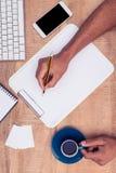Сочинительство бизнесмена на тетради на столе пока держащ кофе Стоковое Изображение RF