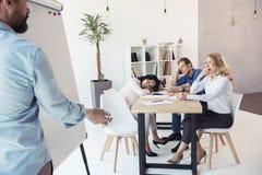 Сочинительство бизнесмена на whiteboard пока его утомленные коллеги сидя на таблице Стоковая Фотография