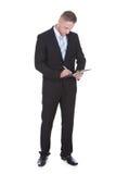 Сочинительство бизнесмена стоящее на handheld доске сзажимом для бумаги Стоковая Фотография RF