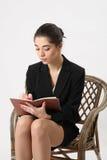 Сочинительство бизнес-леди в тетради Стоковая Фотография