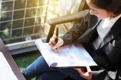 Сочинительство бизнес-леди на доске сзажимом для бумаги снаружи на террасе, на взгляд сверху Стоковое Фото