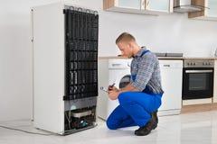 Сочинительство водопроводчика на доске сзажимом для бумаги перед холодильником Стоковые Изображения RF