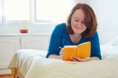 Сочинительство девушки в дневник или планирование ее день Стоковое Фото