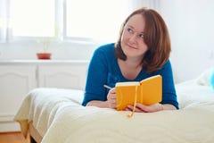 Сочинительство девушки в дневник или планирование ее день Стоковое Изображение RF
