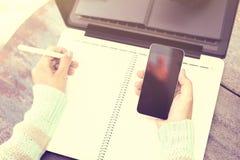 Сочинительство девушки в тетради с сотовым телефоном Стоковое фото RF