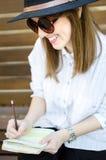 Сочинительство девушки на стенде Стоковые Фото