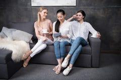 Сочинительство девушки на тетради пока ее друзья выпивая кофе пока сидящ на софе Стоковая Фотография RF