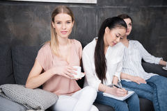 Сочинительство девушки на тетради пока ее друзья выпивая кофе пока сидящ на софе Стоковые Фото