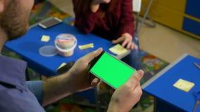 Сочинительство девушки подростка на пост-ем пока молодой человек держит умный телефон с зеленым экраном акции видеоматериалы