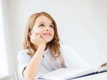 Сочинительство девушки студента в тетради на школе Стоковая Фотография RF