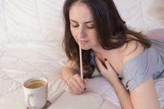 Сочинительство женщины в ее тетради стоковое фото