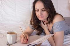 Сочинительство женщины в ее тетради стоковые фото