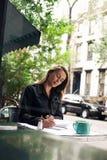 Сочинительство женщины на кафе Стоковое Изображение