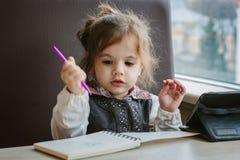 Сочинительство или чертеж девушки маленького ребенка с ручкой в книге scetch Стоковые Фотографии RF