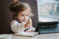 Сочинительство или чертеж девушки маленького ребенка с ручкой в книге scetch Стоковое Изображение RF