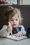 Сочинительство или чертеж девушки маленького ребенка с ручкой в книге scetch Стоковое Изображение