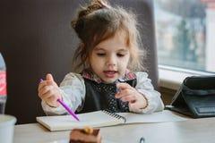 Сочинительство или чертеж девушки маленького ребенка с ручкой в книге scetch Стоковая Фотография
