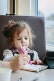 Сочинительство или чертеж девушки маленького ребенка с ручкой в книге scetch Стоковые Фото