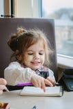 Сочинительство или чертеж девушки маленького ребенка с ручкой в книге scetch Стоковое фото RF