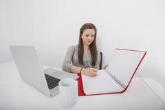 Сочинительство коммерсантки в книге на столе офиса Стоковые Фото