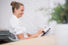 Сочинительство коммерсантки в дневнике на офисе Стоковое Изображение