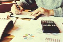 Сочинительство коммерсантки делает примечание и высчитывает о задолженности дома Стоковая Фотография