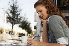 Сочинительство коммерсантки на бумаге на внешнем кафе Стоковое Изображение RF