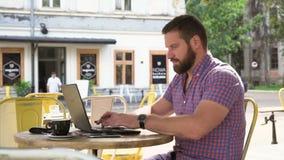 Сочинительство молодого человека на компьтер-книжке в кафе, слайдере сняло справедливо видеоматериал