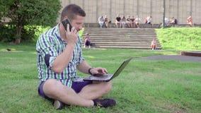 Сочинительство на компьтер-книжке, телефонный звонок молодого человека ответов, усаживание на траве сток-видео
