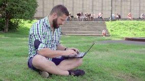 Сочинительство на компьтер-книжке, усаживание молодого человека на траве steadicam сток-видео