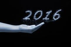 Сочинительство 2016 Нового Года сверкнает фейерверк держа дальше человеческую руку с черной предпосылкой стоковое фото