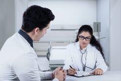 Сочинительство доктора что-то для ее пациента Стоковое Фото