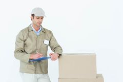Сочинительство работника доставляющего покупки на дом на доске сзажимом для бумаги Стоковая Фотография RF