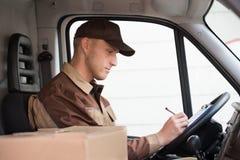 Сочинительство работника доставляющего покупки на дом на доске сзажимом для бумаги в тележке Стоковые Изображения RF